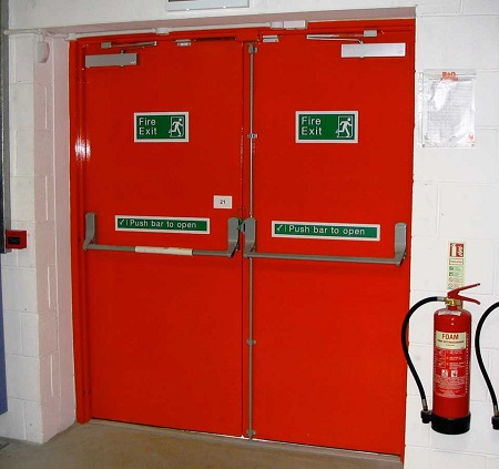 A red-colored fire-rated door with a big metal handle, fire exit, and other text written on it and a fire extinguisher nearby.